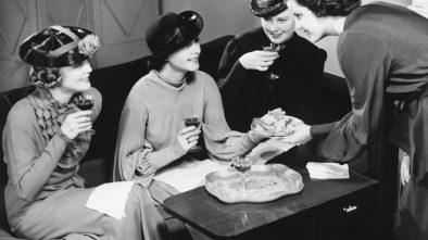 Four women drinking wine, talking in living room
